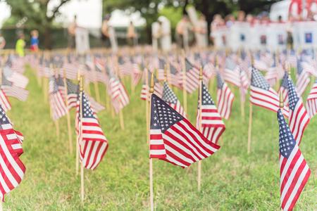 Césped banderas americanas con fila borrosa de personas llevan desfile de pancartas de soldados caídos