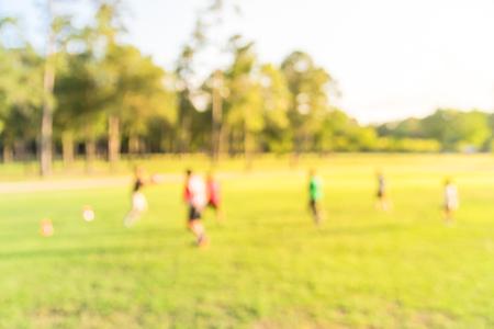 Niños de América Latina de fondo borroso jugando al fútbol en el parque durante la puesta de sol