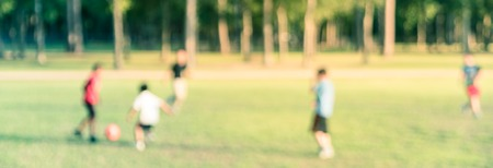Panoramic view blurry background Latin America boys playing soccer at park during sunset