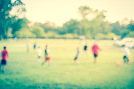 Filtered image blurry background coach playing soccer with boys at park during sunset