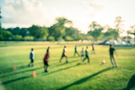 Filtered image blurry background Latin America boys playing soccer at park during sunset