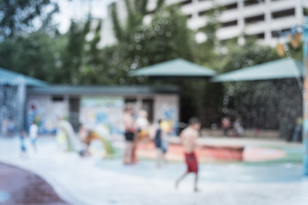 Filtered image blurry background diverse children playing at water splash pad