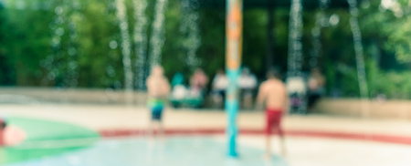 Panorama view blurry background parents and kids enjoy water splash pad at summer time