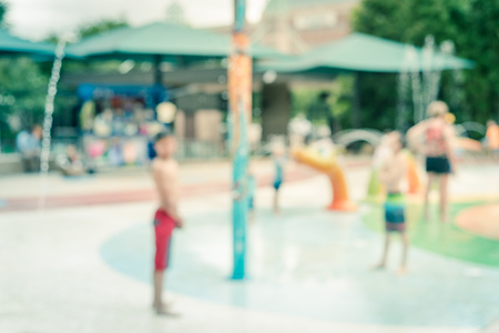 Blurry background parents and kids enjoy water splash pad at summer time