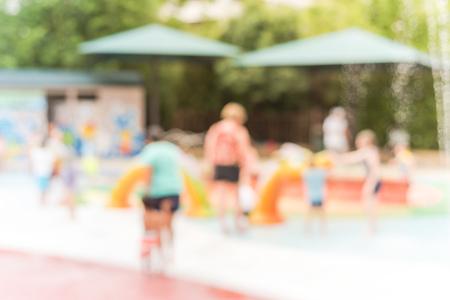 Blurry background diverse children playing at water splash pad in Houston, Texas