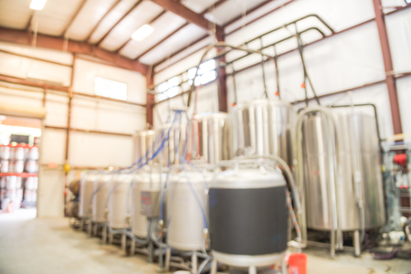 Blurry background fermentation system of beer plant brewing in Texas, USA Stock Photo