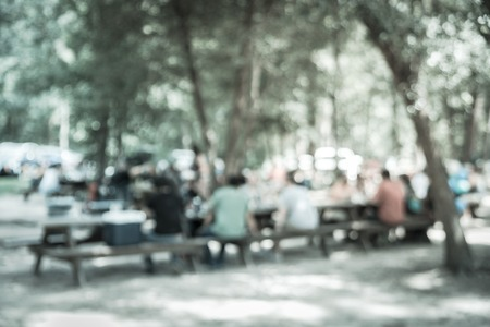 Vintage tone blur image group of people hanging out at semi forest, wooded area of craft brewery in Conroe, Texas, US. Beer garden fill with picnic tables, long benches setup under tall oak trees