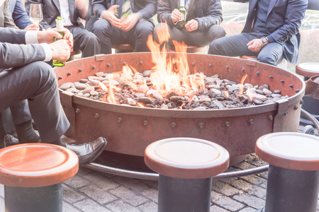 Group of Caucasian businessmen in formal dress gathering over the round fire pit after work in Chicago. Business people in formal dress with watches, leather shoes drinking beer bottle, wine glasses
