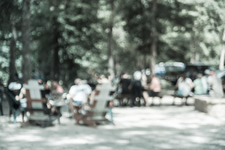 Vintage tone blur image group of people hanging out at semi forest, wooded area of craft brewery in Conroe, Texas, US. Beer garden fill with picnic tables, long benches setup under tall oak trees Stock Photo - 124393017