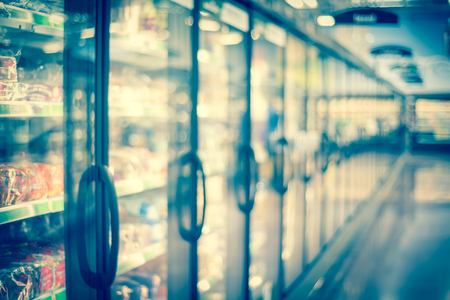 Blurred frozen food section at retail store in America. Huge glass door aisle with variety pack of processed fruit, vegetable, breakfast, appetizer, side, meals, pizza. Food in supermarket background Stock Photo - 124393101