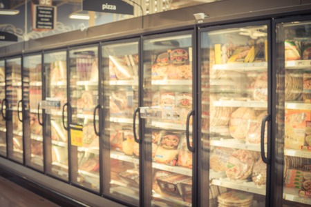 Blurred variety pack of processed pizza at retail store in America. Frozen food section in huge glass door aisle. Freezer full assortment of frozen pizza in local supermarket, defocused background