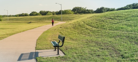 Curved pathway with bench in a hillside urban park near Dallas, Texas, America. Rearview of chubby lady jogging with headphone near lamppost. Imagens