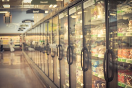 Motion blurred customer shopping for frozen food section at retail store in US. Huge glass door aisle with variety pack of processed fruit, vegetable, breakfast, appetizer, side, meals, pizza