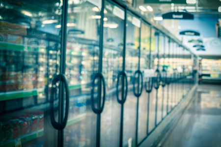 Blurred frozen food section at retail store in America. Huge glass door aisle with variety pack of processed fruit, vegetable, breakfast, appetizer, side, meals, pizza. Food in supermarket background Stock Photo - 124393177