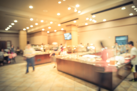Blurred multiethnic customers line up and choosing traditional foods, chef prepares to serve. Defocused large Vietnamese buffet restaurant in Houston, Texas, US. Wall mounted TV showing today menu