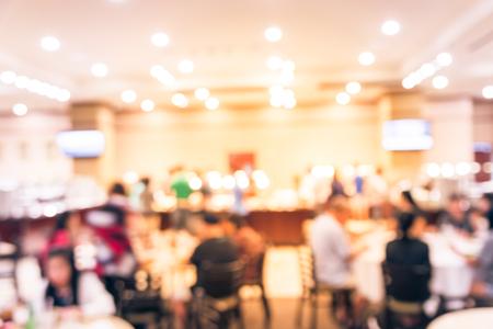 Movimiento borroso personas disfrutan de comida fresca en la mesa de comedor redonda mientras que otros eligen comida en el puesto de buffet. Gran restaurante buffet vietnamita en Houston, Texas, EE. UU. TV de pared que muestra el menú de hoy Foto de archivo