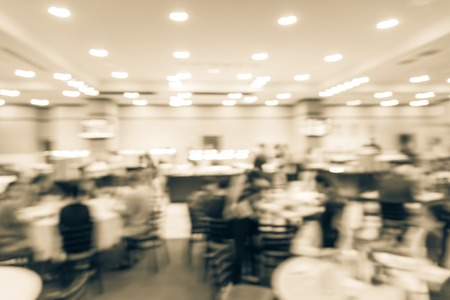 Vintage tone motion blurred people enjoy fresh meal on round dining table while other choosing food at buffet stand. Vietnamese buffet restaurant at Texas, US. Wall mounted TV showing today menu