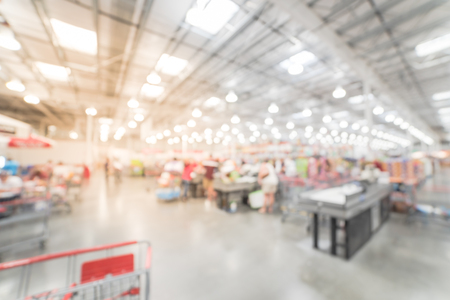 Blurred motion long line of customers at check-out counter in America. Concept of busy shoppers waiting at wholesale store during weekend. Stock Photo