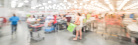 Panorama view motion blurred long line of customers at check-out counter in America. Concept of busy shoppers waiting at wholesale store during weekend