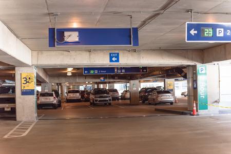 2 hour parking overhead neon sign at indoor American airport parking lot displays number of available parking spaces. Available empty spots display counter information