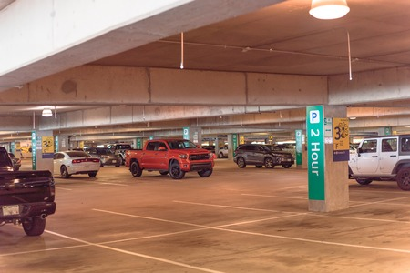 Garage parking at American airport with indicators guidance system. People can look for a parking spot by seeing little overhead green lights. Intelligent sensors IoT, real time ultrasonic direction