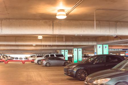 Parcheggio in garage all'aeroporto americano con sistema di guida a indicatori. Le persone possono cercare un parcheggio vedendo piccole luci verdi in alto. Sensori intelligenti IoT, direzione ultrasonica in tempo reale Archivio Fotografico