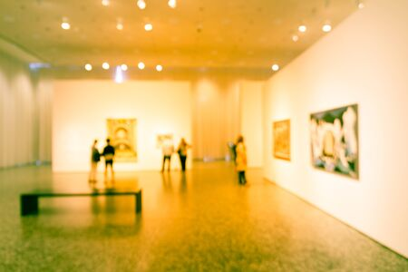 Filtered image blurry background people looking at fine art display at museum in USA