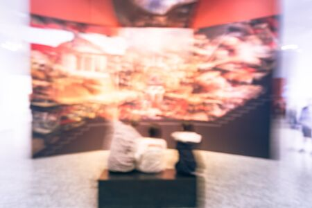 Blurry background people looking at fine art display at museum in America Stock Photo