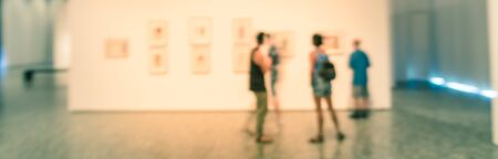 Panorama view blurry background people looking at fine art display at museum in USA