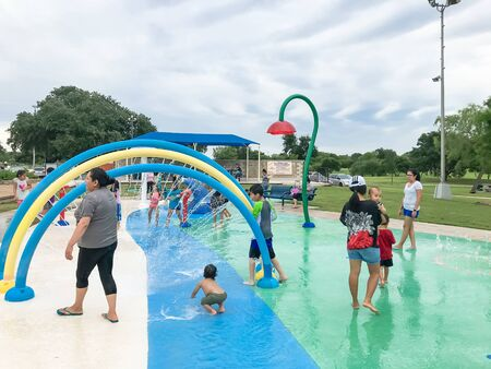 Multicultural kids and parent playing at splash park under summer stormy weather