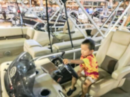 Abstract blurred Asian toddler boy try driving the boat at showroom large outdoor store in Texas, America. Boat buying and servicing concept Banque d'images