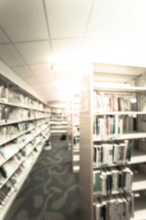 Blurry background aisle of bookshelf with step stool at American public library