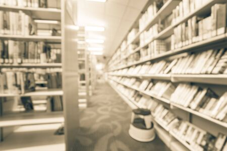 Filtered image blurry background aisle of bookshelf with step stool at public library in USA 免版税图像 - 125118496