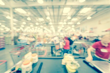 Filtered image blurry background busy checkout line at wholesale big-box store in America