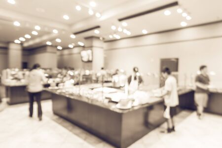 Vintage tone blurred multiethnic customers line up and choosing traditional foods, chef prepares to serve. Large Vietnamese buffet restaurant in Texas, US. Wall mounted TV showing today menu