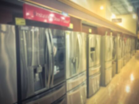 Blurry background rows of brand new French door refrigerators with ice makers
