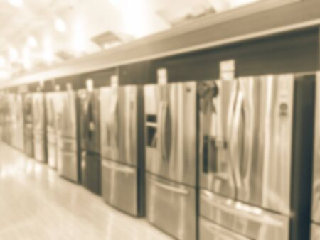 Filtered image blurry background rows of brand new French door refrigerators with ice makers