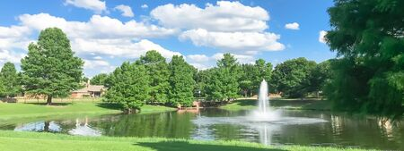 Panorama view beautiful pond with water fountain in small neighborhood North of Dallas, Texas, America. Lake house surrounding by matured trees, green grass lawn and cloud blue sky