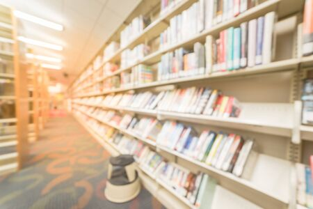 Blurred, wide perspective view aisle of bookshelf with reading step stool at public library in America. Continuing education concept.