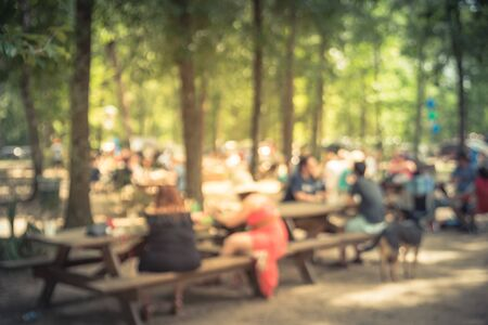 Blur image group of people hanging out at semi forest, wooded area of craft brewery in Conroe, Texas, US. Beer garden fill with picnic tables, long benches setup under tall oak trees. Park activities.