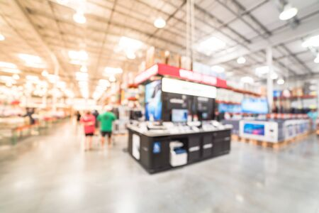 Motion blurred customer shopping for variety of modern smart phones at cell phone department. Defocused background of technology inventory, hypermarket, wholesale, distribution warehouse, storehouse Stock Photo