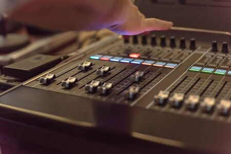 Close-up buttons equipment for sound mixer control. Mixer for musician DJ and sound engineers. Mixing DJ remote with colorful neon light. Night club, nightlife concept