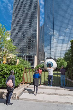 DALLAS, TX, USA-MAY 3, 2019: Visitors taking photo with Giant Eyeball streaky red veins, by Tony Tasset in 2007. 30-ft. tall, realistically rendered fiberglass sculpture of human in a fenced garden Editöryel
