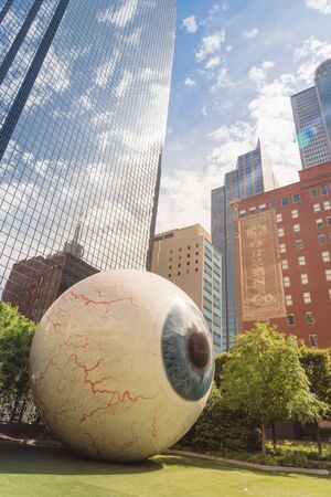 DALLAS, TX, USA-MAY 3, 2019: Hyper-realistic eyeball with streaky red veins created by artist Tony Tasset in 2007. 30-ft. tall, realistically rendered fiberglass sculpture of human in a fenced garden