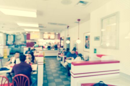 Vintage tone blurred image a compact fast food restaurant in Austin, Texas, USA. People serving sauce, ketchup and enjoying lunch with burgers, fried fries and sugar drink