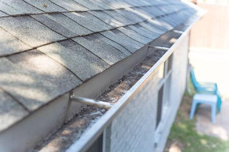 Gutter near roof shingles of residential house full of dried leaves and dirty need to clean-up. Gutter cleaning and home maintenance concept Stock Photo