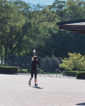 Back view of healthy woman in fall sportswear running in urban park. Healthy woman with headphones exercise at daytime in downtown Chicago