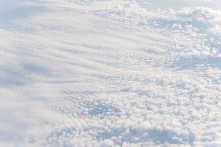 Beautiful and unusual Altocumulus or Cirrocumulus cloud formation seen from airplane window at sunrise. Skyline view above the clouds from the air Standard-Bild - 129318806