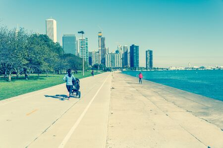 Vintage tone rear view of fit Asian lady running pushing stroller along shoreline of Michigan Lake with downtown Chicago skylines in background. Fit sportswear woman exercise outdoor at fall daytime