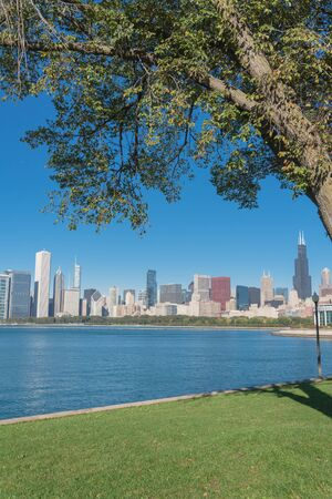 Lakefront Chicago skylines with trees from the park of Northerly Island along the shore of Lake Michigan Standard-Bild - 129318820